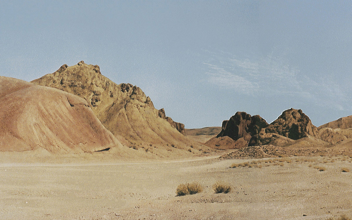 Desert landscape of mountains and barren lands during the day with no  clouds that can be front lit only